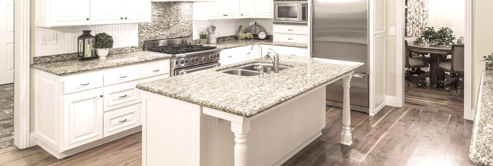 Virtuvė iš akmens dirbinių: akmeninis pilkas stalviršis stalui, virtuvės paviršiams. Gražus virtuvės interjero pavyzdys